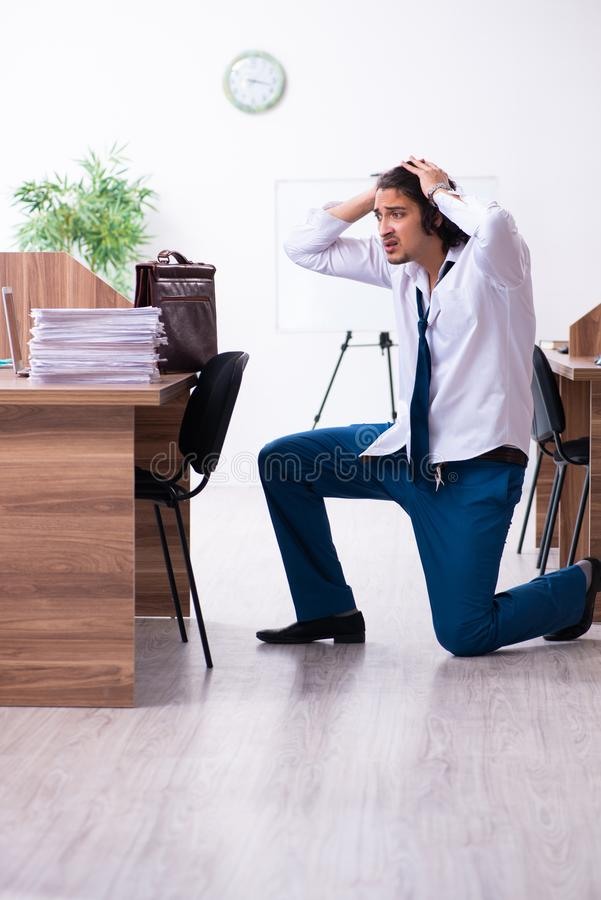 Young male employee unhappy with excessive work stock images