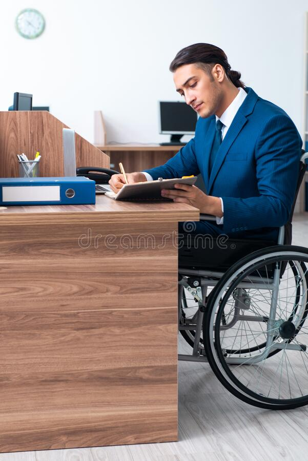 Young male employee in wheel-chair stock image