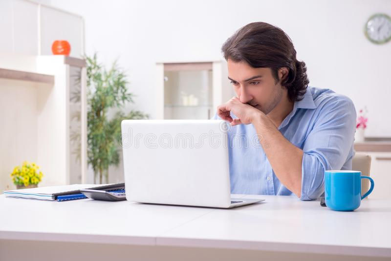 Young male employee working at home. The young male employee working at home stock photo