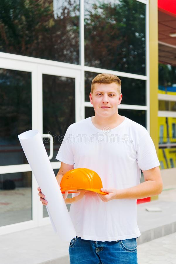 Young Male Engineer Construction worker holding building plan . Construction worker with plan of work on the background of freshly royalty free stock image