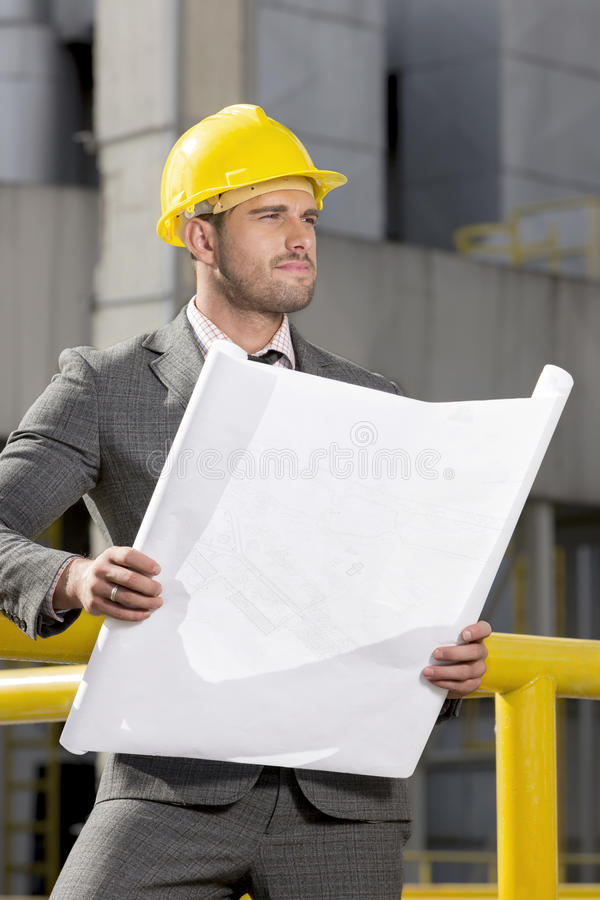 Young male engineer holding blueprint while looking away at construction site royalty free stock image