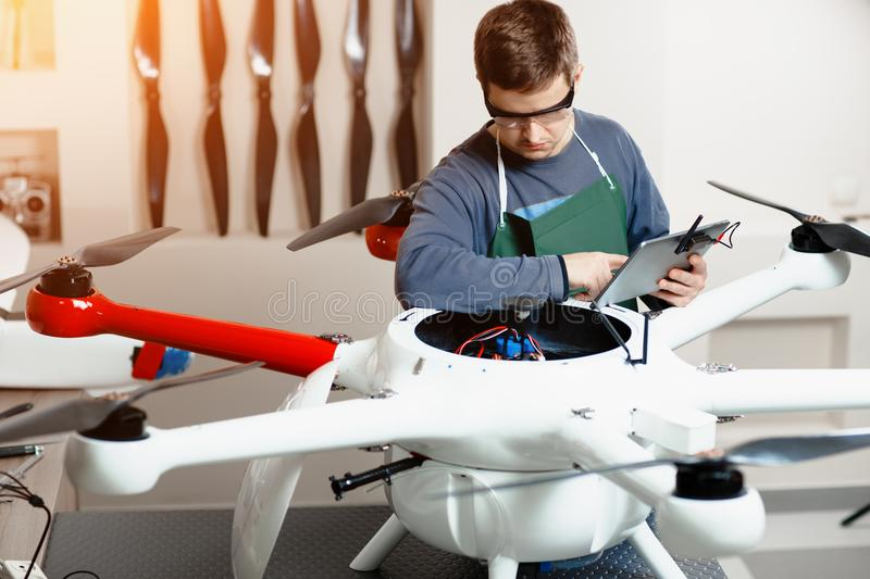 Young Male Engineer or Technician with Holding Tablet in His Hands Programs Drone. royalty free stock photos