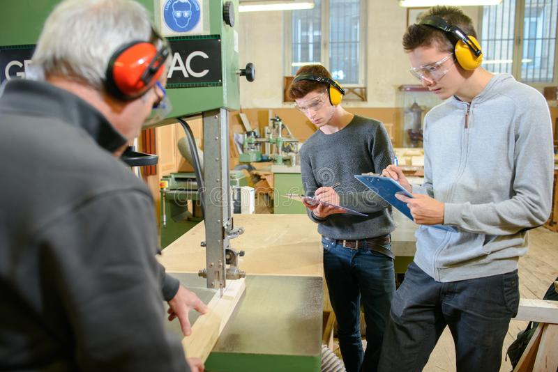 Young male engineers in factory using milling machine stock photos