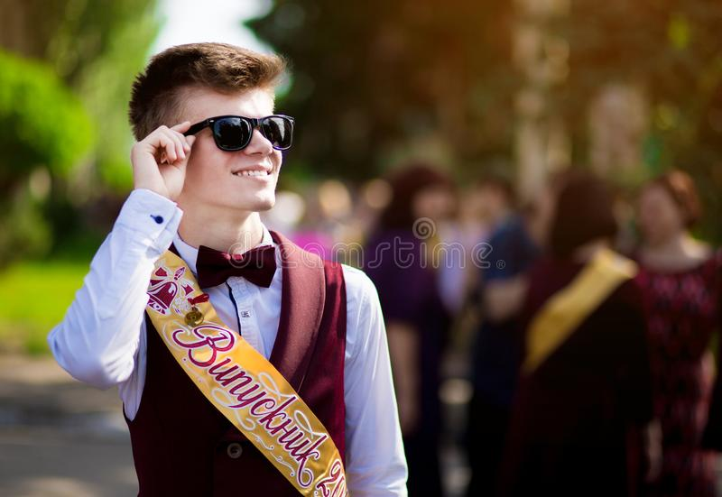 Young male excellence student dressed in school uniform. Campus as a background. Boy in sunglasses cheerfully smiling. royalty free stock photography