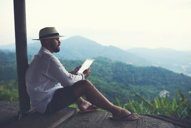 Young male explorer is using digital tablet while admiring wild mountains nature. Man wanderer enjoying amazing jungle landscape and holding in hands portable stock photos