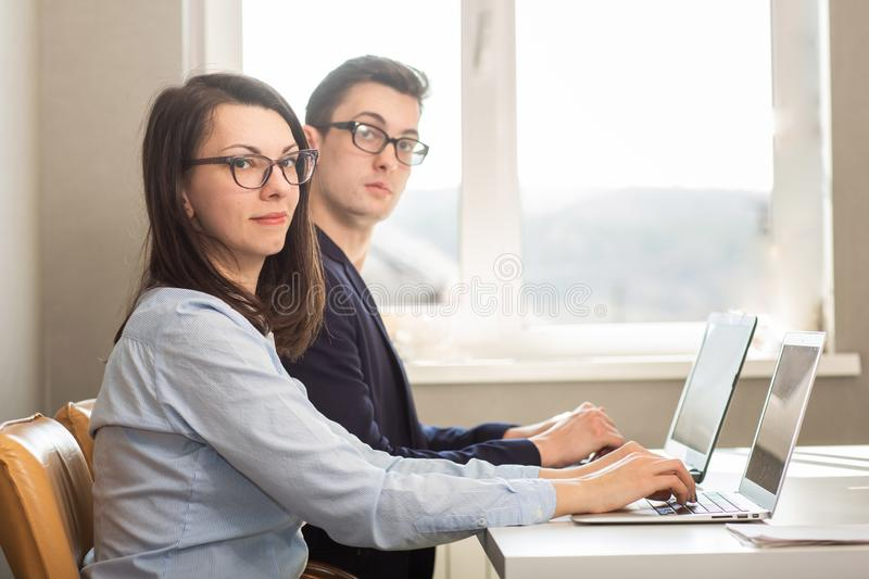 Young male and female business partners sitting behind a computer monitor.  royalty free stock images