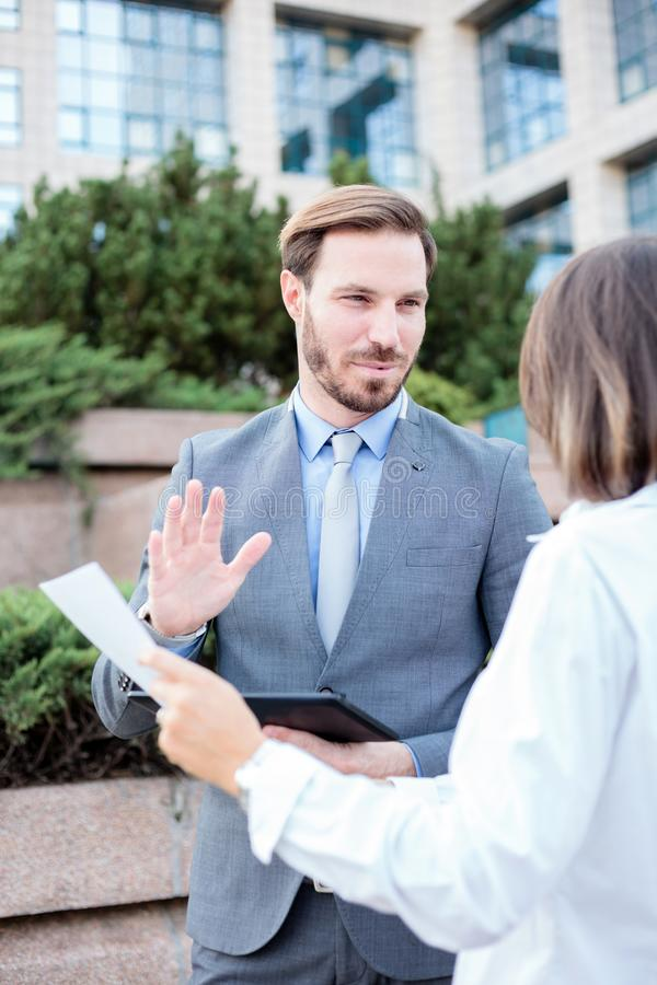 Young male and female business people talking in front of an office building, having a meeting and discussing royalty free stock photo