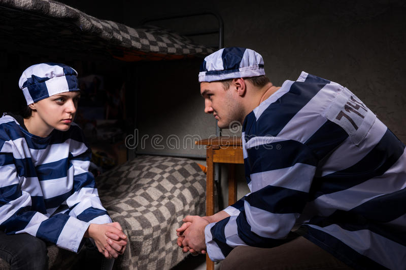 Young male and female prisoners wearing prison uniform sitting a. Young male and female prisoners wearing prison uniform sitting near bedside table and looking royalty free stock photos