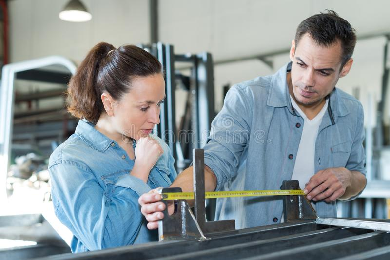Young male and female workers measuring wood in workshop royalty free stock photos