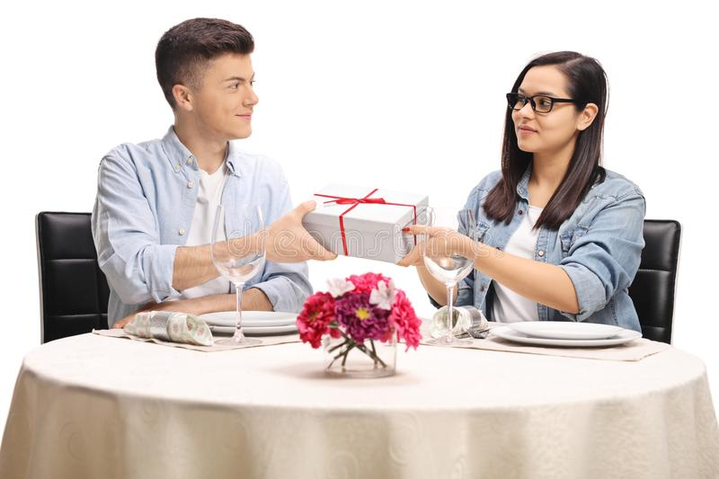 Young male giving a gift box to a female at a restaurant table stock image