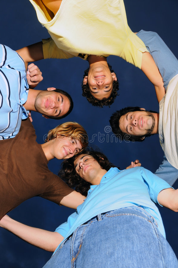 Young male group. Portrait of young trendy group of friends embracing - from below stock image