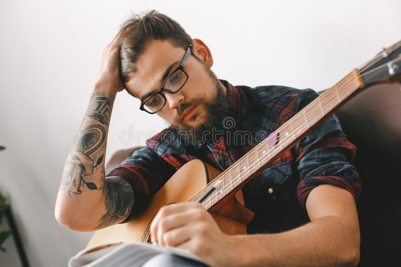 Young guitarist hipster at home with guitar sitting writing melody close-up. Young male guitarist hipster indoors sitting on the coach holding guitar writing royalty free stock image