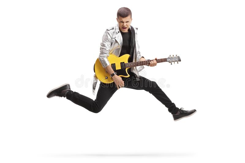 Young male guitarist jumping and playing. Full length shot of a young male guitarist jumping and playing isolated on white background royalty free stock photo