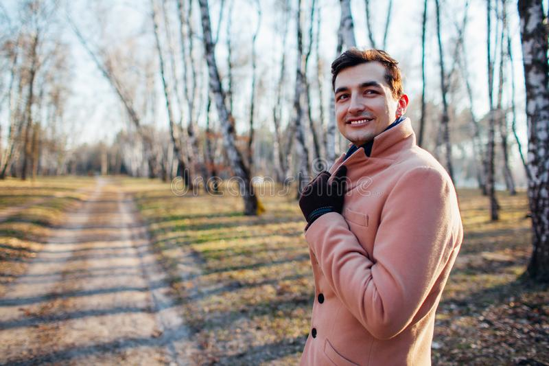 Young male walking in the forest in nature in a cream coat. Young male gulet in the woods in nature in a cream coat stock photos