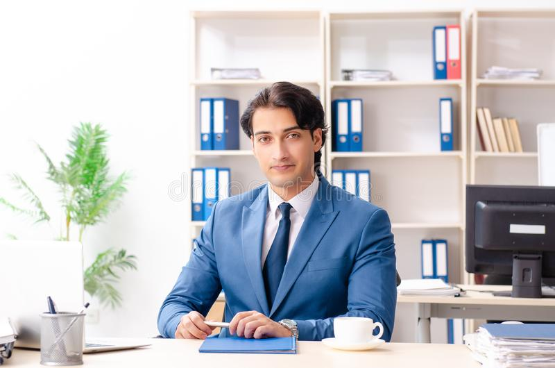 The young male handsome employee sitting in the office stock photography