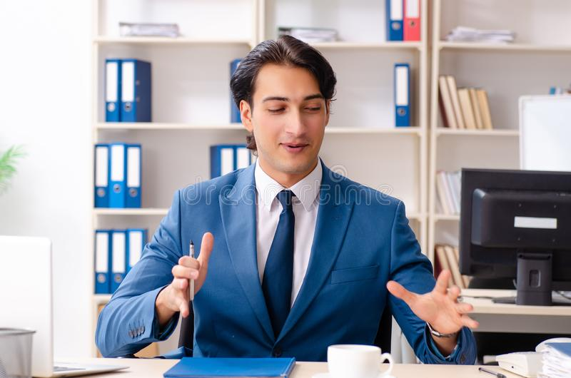 The young male handsome employee sitting in the office royalty free stock photos