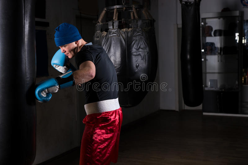 Young male in a hat and boxing gloves training with boxing punch stock photo