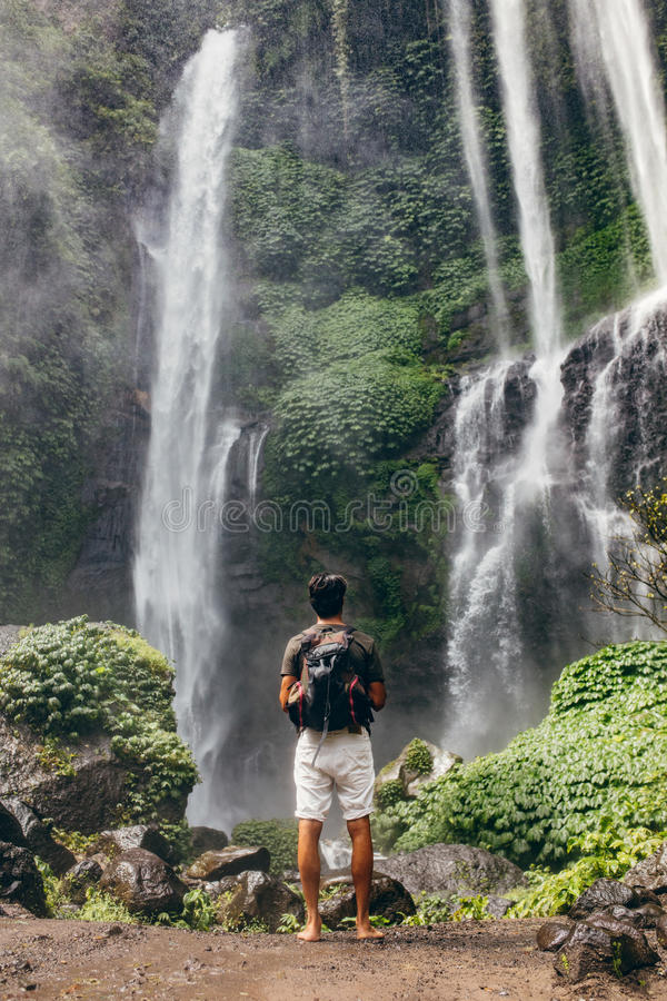 Young male hiker looking at waterfall stock photography