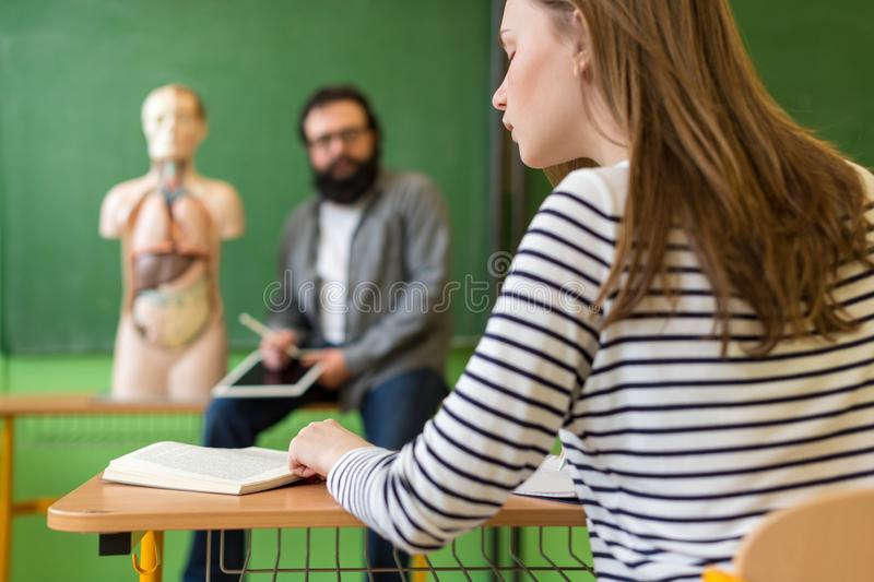 Young male hispanic teacher in biology class, holding digital tablet and teaching human body anatomy, using artificial body model. stock images