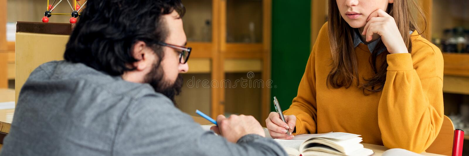 Young male hispanic teacher helping his student in chemistry class. Education, Tutoring and Encouragement concept. stock photo