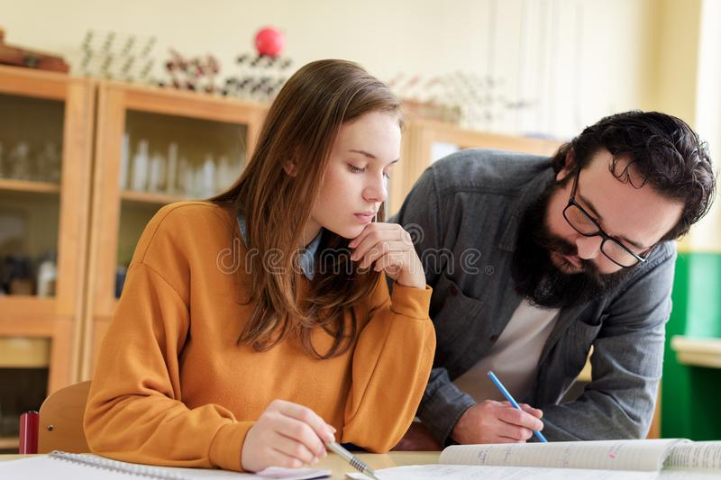 Young male hispanic teacher helping his student in chemistry class. Education, Tutoring concept. royalty free stock photo