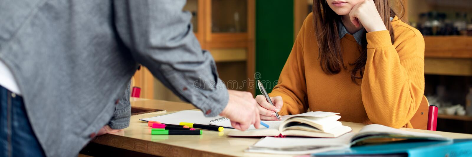 Young male hispanic teacher helping his student in chemistry class. Education, Tutoring and Encouragement. Young male hispanic teacher helping his student in royalty free stock photography