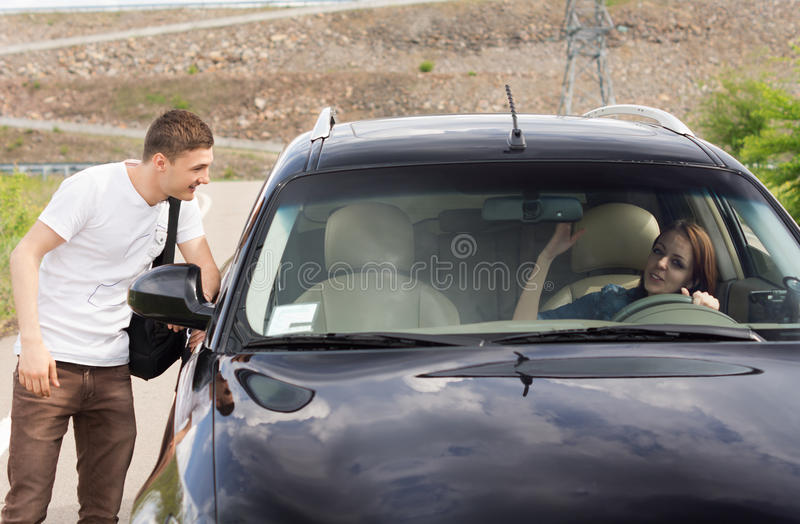 Young male hitchhiker looking for a lift stock image