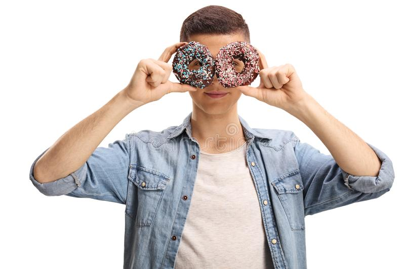 Young male holding donuts in front of his eyes royalty free stock images