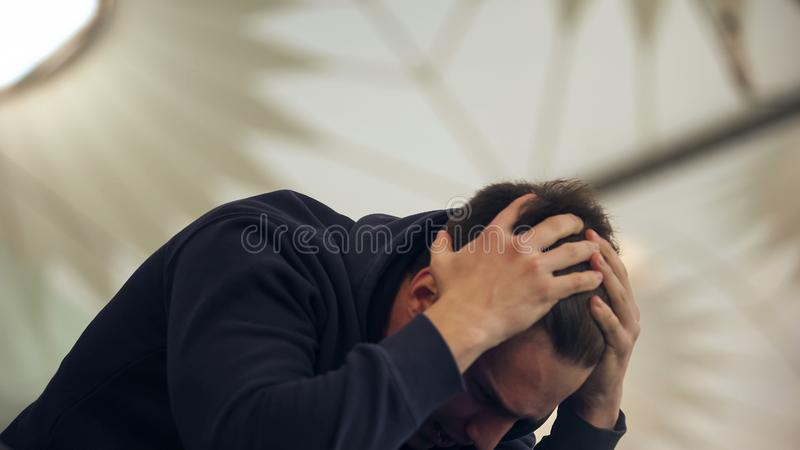 Young male holding head, suffering from hangover after night party, vomiting royalty free stock images