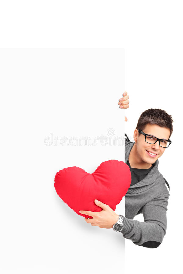 Young male holding a red heart shaped pillow. And a blank banner isolated on white background royalty free stock images