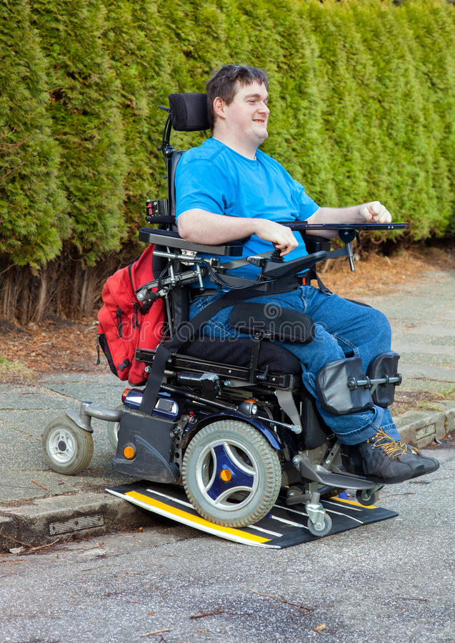 Young male infantile cerebral palsy sufferer. Spastic young man with infantile cerebral palsy caused by birth complications using a mobile ramp on a kerb to stock photography