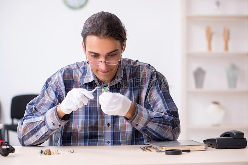 Young male jeweler at workshop stock images