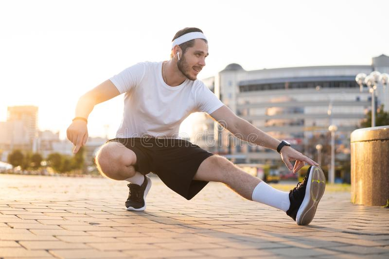 Young male jogger athlete training and doing workout outdoors in city. stock photos