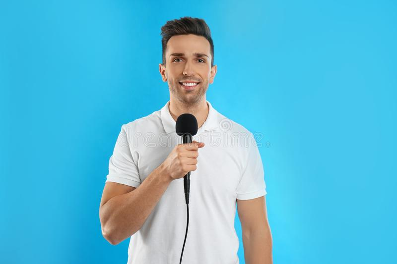 Young male journalist with microphone on background royalty free stock photography
