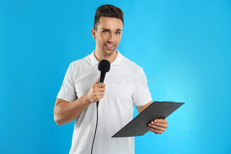 Young male journalist with microphone and clipboard on background stock photos