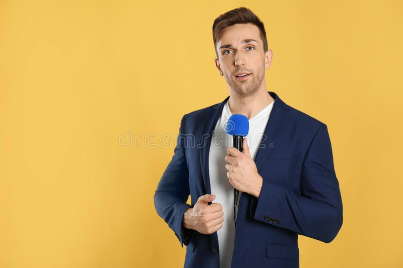 Young male journalist with microphone on background. Space for text stock photography