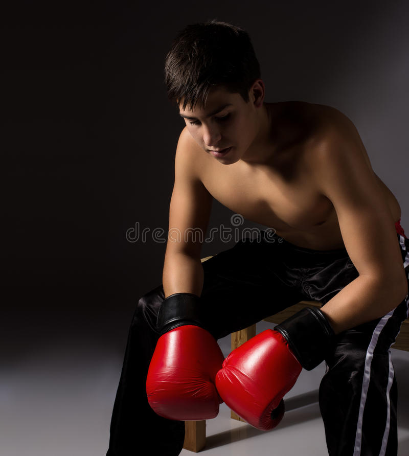 Young male kickboxer. Young handsome male caucasian kickboxer wearing red boxing gloves and kickboxing gear isolated on a neutral background royalty free stock photo