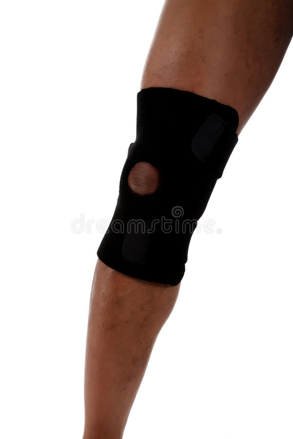 Young male leg, African American. Young African American male leg with the knee in the protective knee-brace. Studio shot. White background stock photography