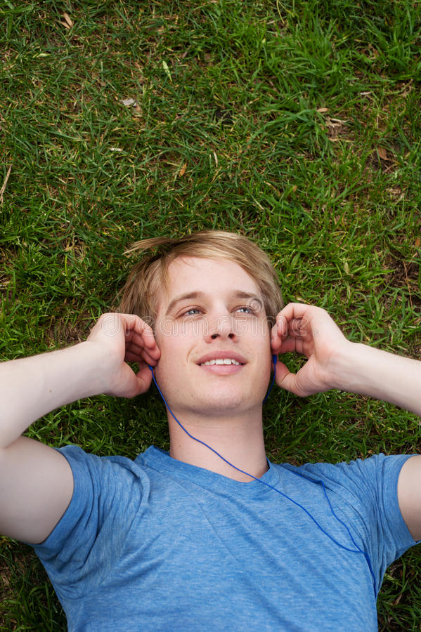 Young male lying in the grass stock photography