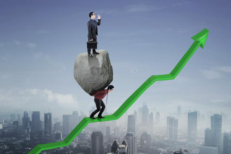 Young manager with his partner on upward arrow. Young male manager shouting above stone while his partner stepping on an upward arrow stock photography