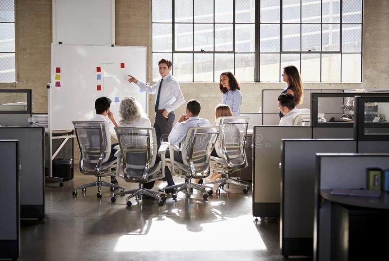 Young male manager using whiteboard in a business meeting royalty free stock image