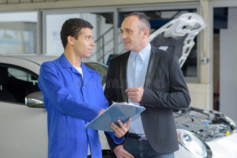 Young male mechanic talking to mature male customer stock photography