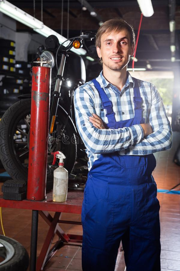 Young male mechanic working in auto repair shop. Male mechanic working in auto repair shop stock photo