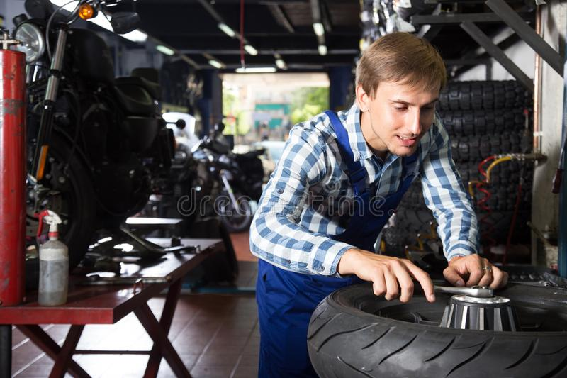 Young male mechanic working in auto repair shop royalty free stock image