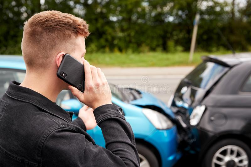 Young Male Motorist Involved In Car Accident Calling Insurance Company Or Recovery Service stock photography