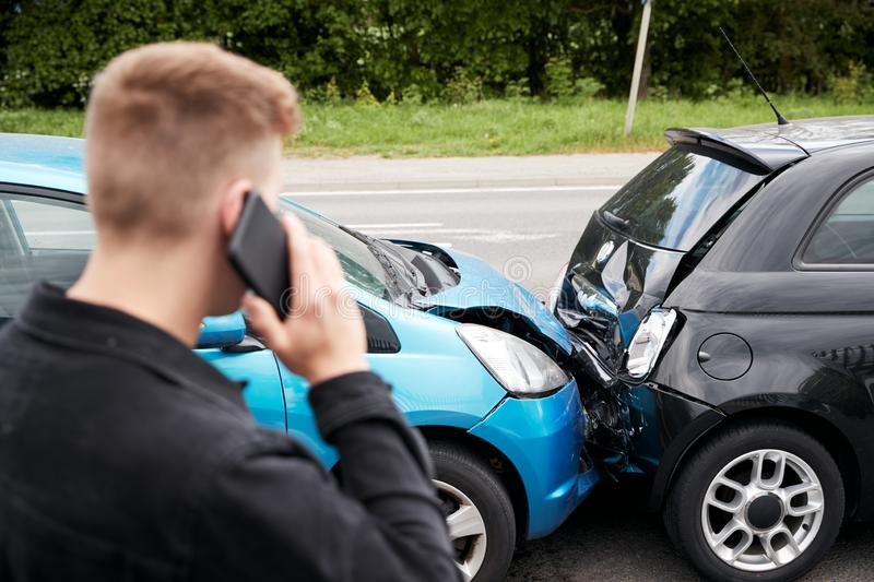Young Male Motorist Involved In Car Accident Calling Insurance Company Or Recovery Service stock photos