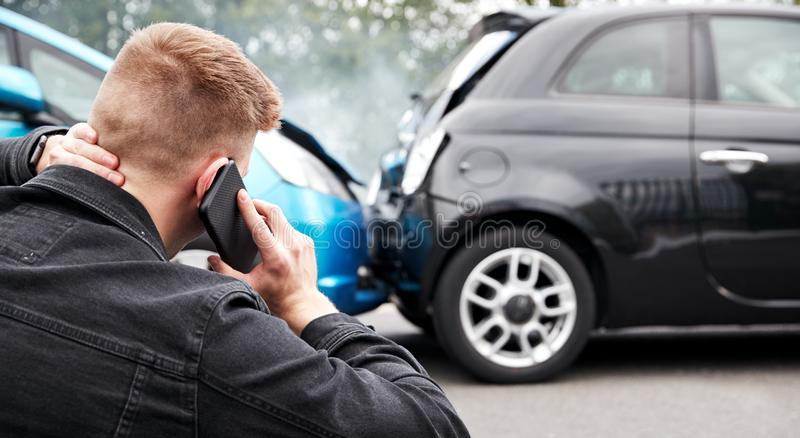 Young Male Motorist Involved In Car Accident Calling Insurance Company Or Recovery Service stock images