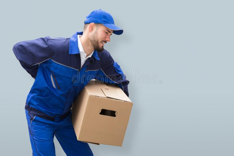 Mover Suffering From Backache While Carrying Parcel stock photos