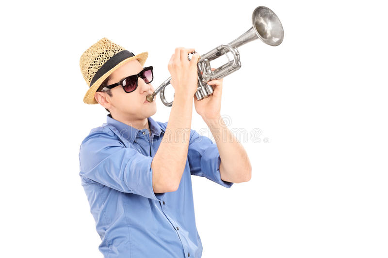 Young male musician blowing into a trumpet. Isolated on white background royalty free stock images