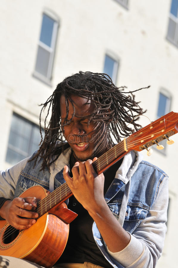 Young male musician playing the guitar. Young African American musician playing a classic guitar in the city royalty free stock photography
